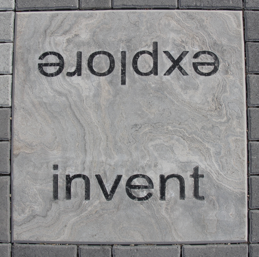 Paving stone engraved with words: invent, explore.